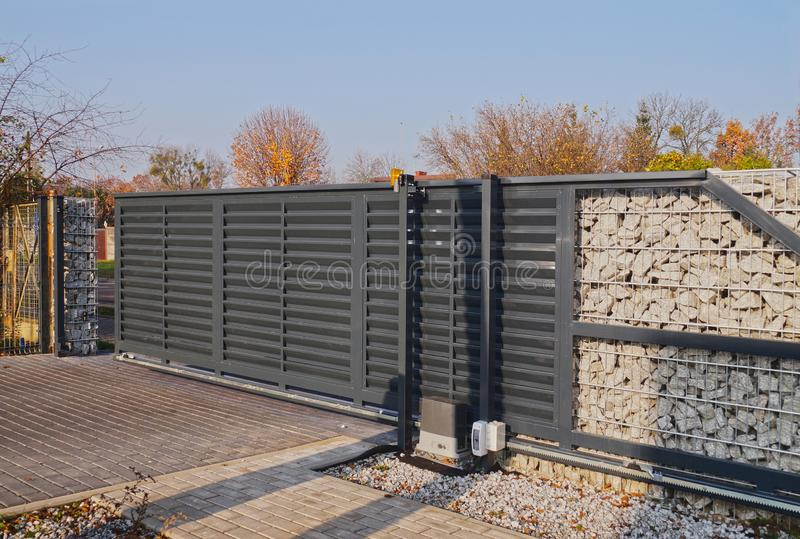 Gabion. Automatic entrance gate used in combination with a wall made of gabion. Automatic entrance gate used in combination with a wall made of gabion stock photo