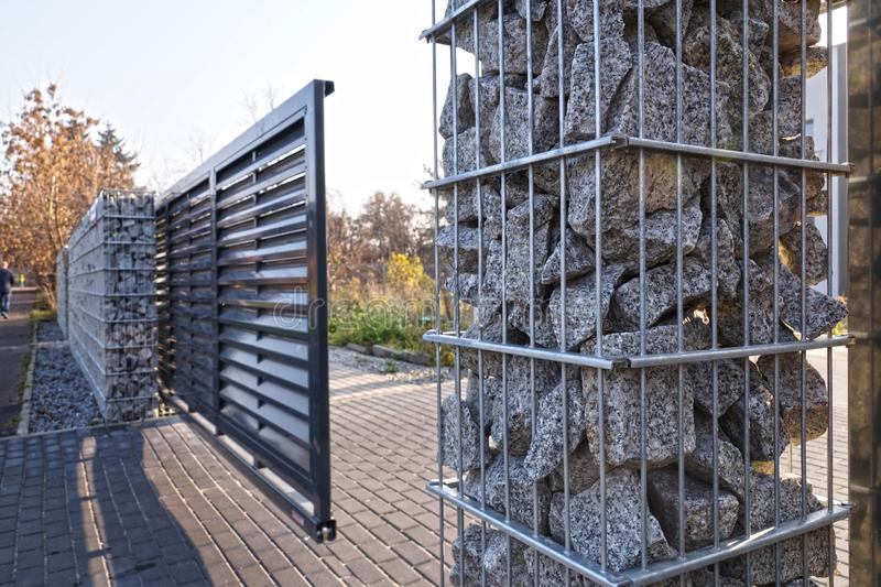Gabion. Automatic entrance gate used in combination with a wall made of gabion. Automatic entrance gate used in combination with a wall made of gabion royalty free stock photo