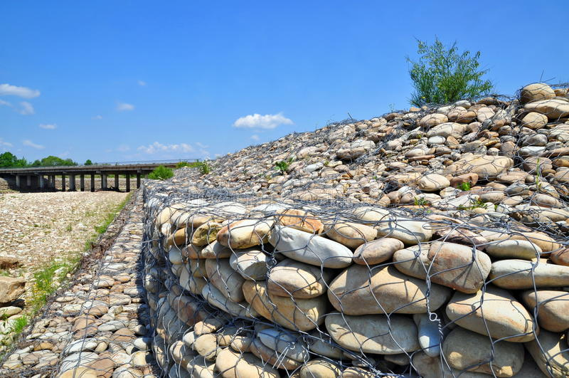 Gabion on the bank of the river stock photo