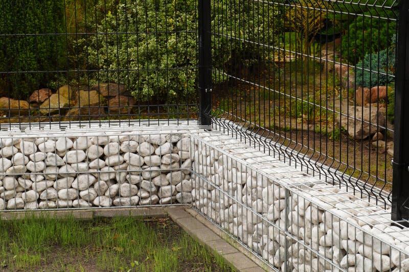 Gabion Uma cerca de aço combinou com uma baixa parede feita dos gabions f imagem de stock