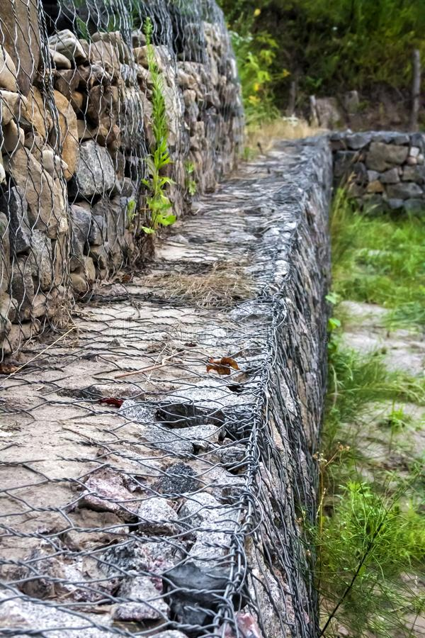 Gabion wall - stones in wire mesh used for erosion control stock photo