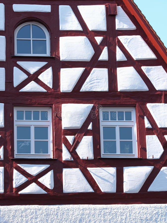 Gable and facade details of an old timber frame medieval house with white render and red beams. In Nuermberg 2016 royalty free stock photos