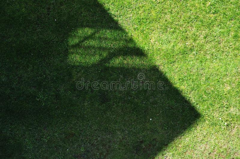 Gable with window casting shadow on lawn stock images