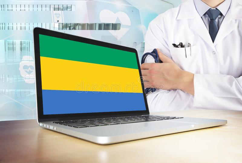 Gabon healthcare system in tech theme. Gabonese flag on computer screen. Doctor standing with stethoscope in hospital. Cryptocurrency and Blockchain concept stock photo