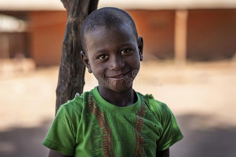 Portrait of of a young boy, in the village of Mandina Mandinga in the Gabu Region, Guinea Bissau. Gabu Region, Republic of Guinea-Bissau - February 7, 2018 royalty free stock photo