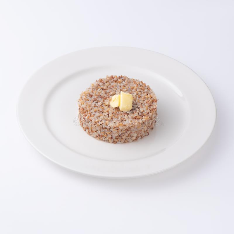 Gachas de avena cocinadas del alforfón en la placa Aislado en un fondo blanco, fotografía de archivo libre de regalías