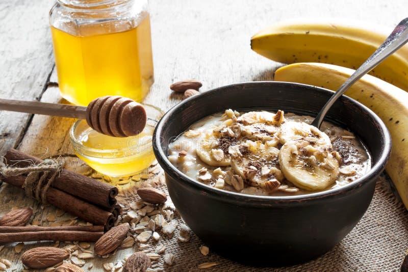 Gachas de avena de la harina de avena en cuenco de cerámica con una cuchara Desayuno sano imágenes de archivo libres de regalías