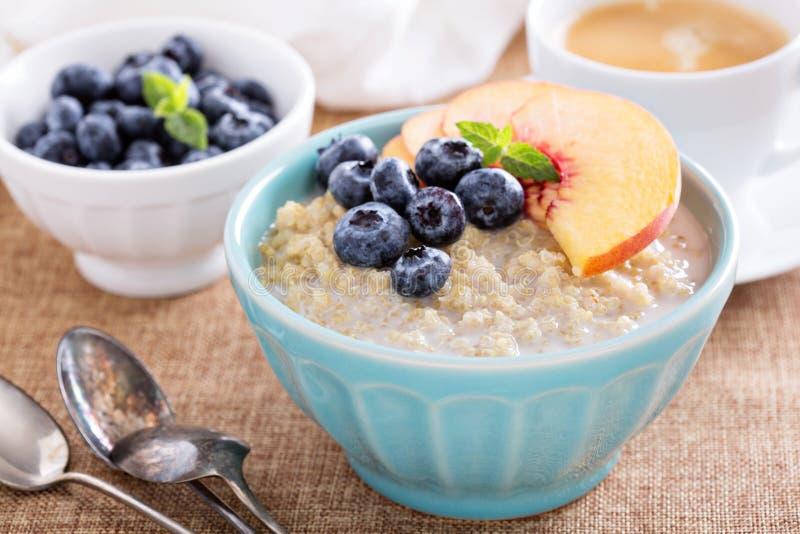 Gachas de avena de la quinoa del desayuno con las frutas frescas fotos de archivo libres de regalías