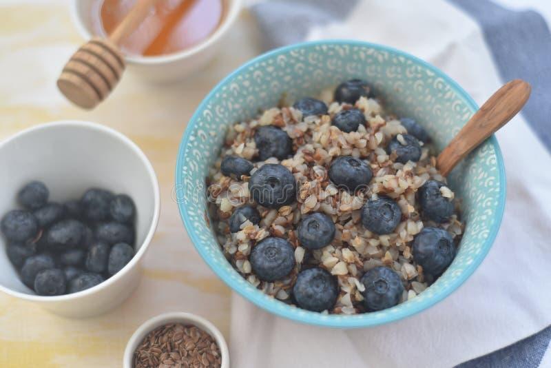 Gachas de avena del alforfón en un cuenco con las semillas y los arándanos de lino comida sana del oncept, detox, dieta, desayuno foto de archivo libre de regalías