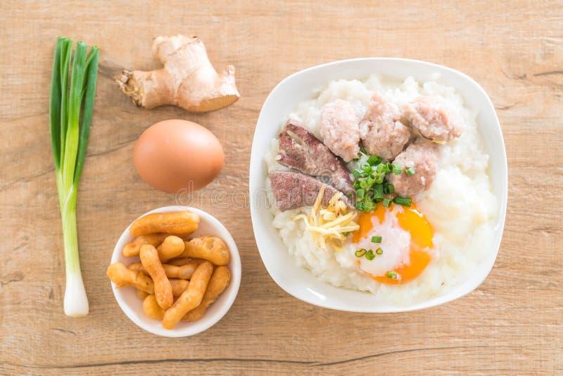 Gachas de avena del arroz con cerdo y el huevo foto de archivo libre de regalías