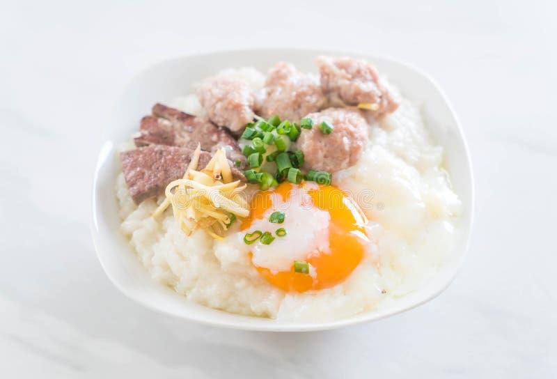 Gachas de avena del arroz con cerdo y el huevo fotografía de archivo