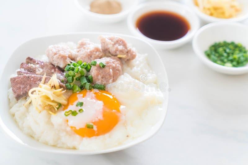 Gachas de avena del arroz con cerdo y el huevo imagenes de archivo