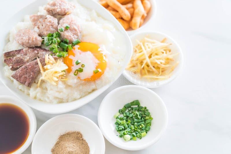 Gachas de avena del arroz con cerdo y el huevo imagen de archivo