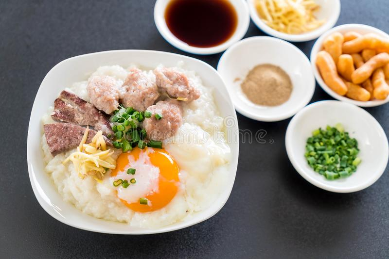 Gachas de avena del arroz con cerdo y el huevo imagen de archivo libre de regalías