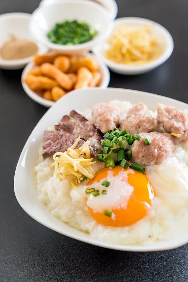 Gachas de avena del arroz con cerdo y el huevo fotos de archivo libres de regalías