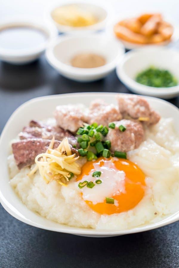 Gachas de avena del arroz con cerdo y el huevo fotos de archivo