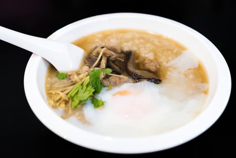 Gachas de avena del arroz con el huevo del cerdo y la seta de shiitake fotos de archivo