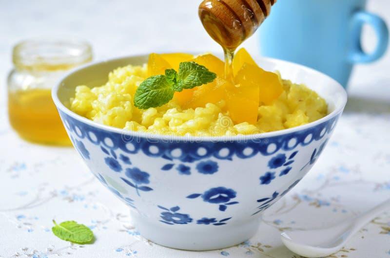 Gachas de avena del arroz de la leche con la calabaza y la miel imagen de archivo libre de regalías