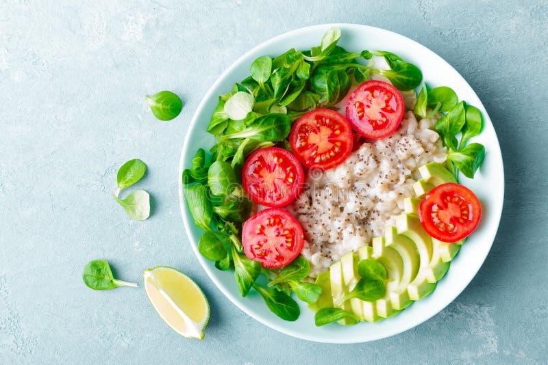 Gachas de avena de la harina de avena con el aguacate y la ensalada vegetal de tomates y de la lechuga frescos Desayuno dietético fotos de archivo