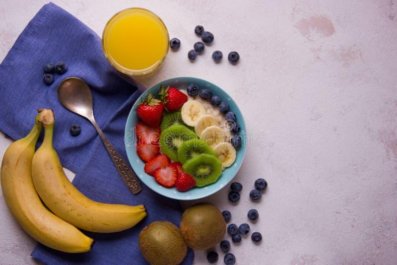 Gachas de avena de la harina de avena con los arándanos, la fresa, el plátano y el kiwi en cuenco foto de archivo