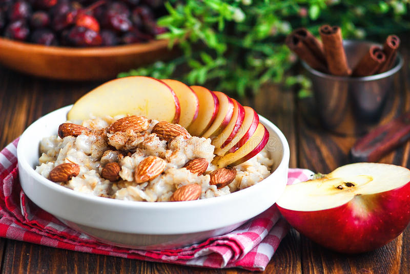Gachas de avena orgánicas de la harina de avena en el cuenco de cerámica blanco con la manzana, la almendra, la miel y el canela  imagen de archivo