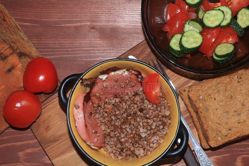 Gachas de avena orgánicas naturales del alforfón en un pote de arcilla, huevos revueltos y una ensalada con los tomates foto de archivo