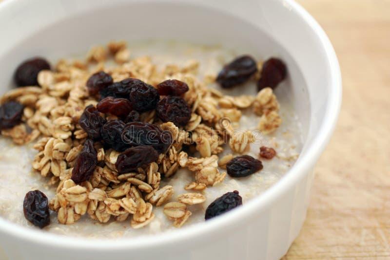 Gachas de avena sanas de la harina de avena del desayuno con el Granola y las pasas orgánicos foto de archivo libre de regalías