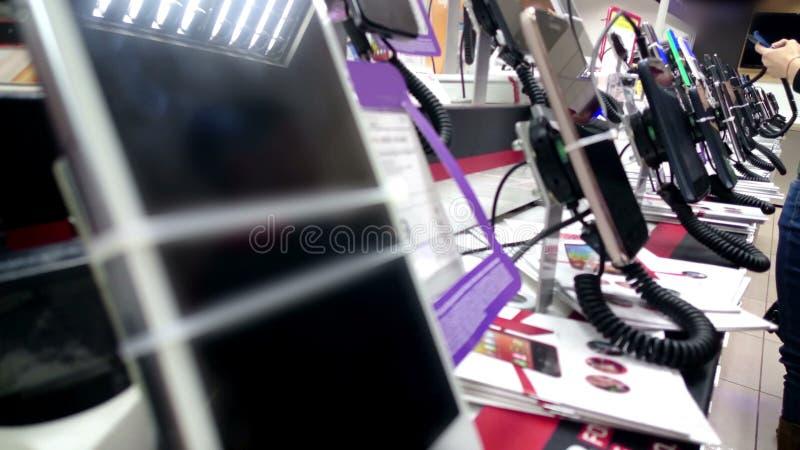 Gadżet sala wystawowa przy elektronika sklepem, nabywcy bada smartphones i wybiera obrazy stock