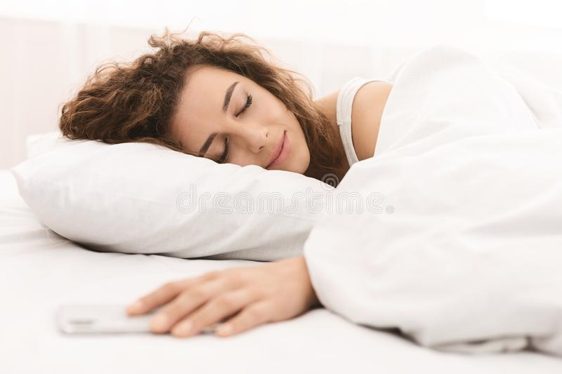 Young woman sleeping and holding smartphone in bed stock photos