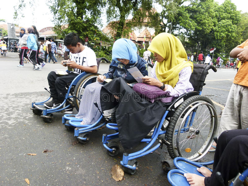 Gadget. Adolescents with disabilities are using the gadget in the city of Solo, Central Java, Indonesia royalty free stock images
