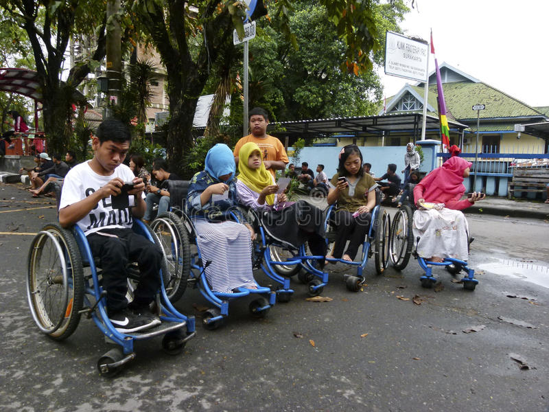 Gadget. Adolescents with disabilities are using the gadget in the city of Solo, Central Java, Indonesia royalty free stock image