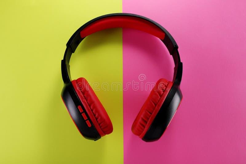 Gadget för trådlösa Bluetooth-hörlurar i färgad bakgrund arkivbild
