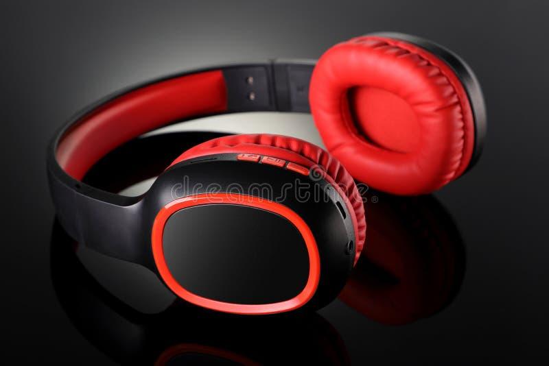 Gadget för trådlösa Bluetooth-hörlurar i svart reflekterande bakgrund royaltyfri foto