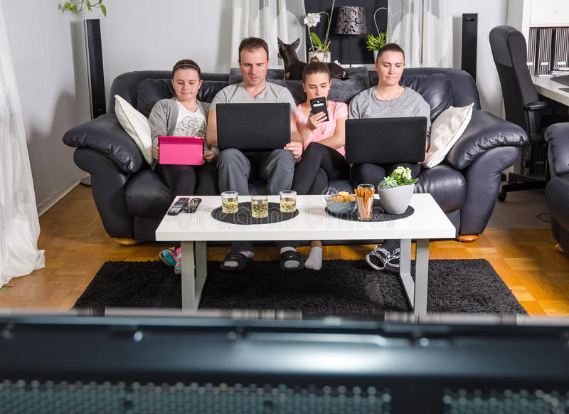 Gadget family in modern time. Gadget family spending time in front of tv stock photo
