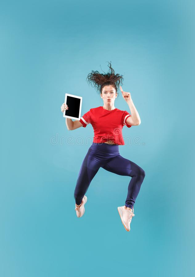 Image of young woman over pink background using laptop computer or tablet gadget while jumping. royalty free stock photo