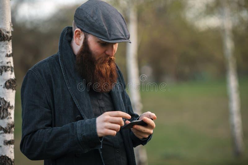 Gadgetmens Openluchtportret van een jonge brutale witte kerel met grote baard en in een uitstekend GLB die Internet op smartphone royalty-vrije stock fotografie
