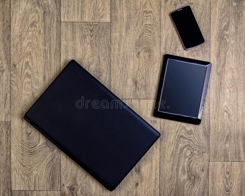 Gadgets on wooden background, top view, laptop, smartphone, tablet royalty free stock photography