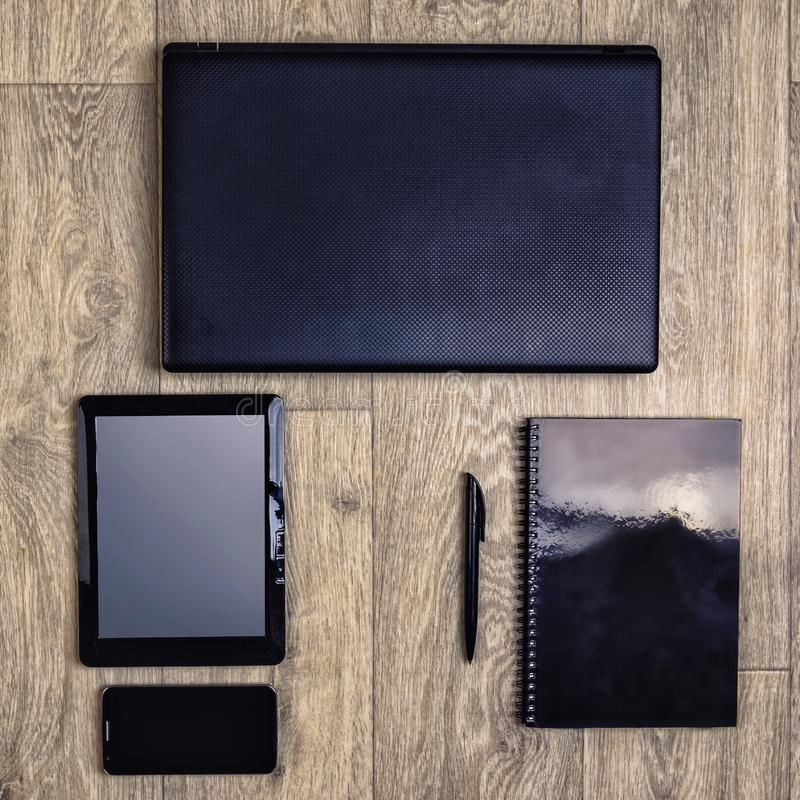 Gadgets on wooden background, top view, laptop, smartphone, tablet, pen stock photography