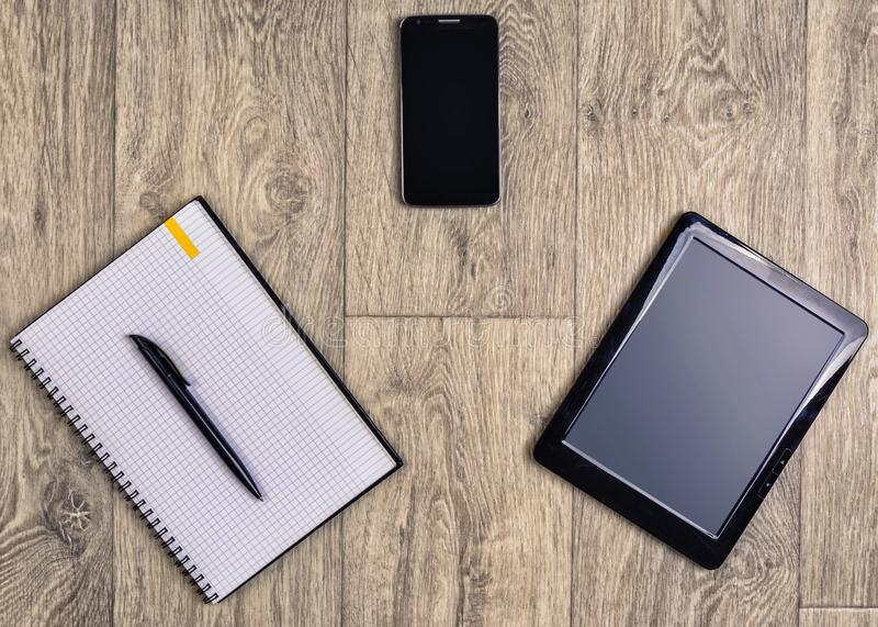 Gadgets on wooden background, top view, pen, smartphone, tablet stock images