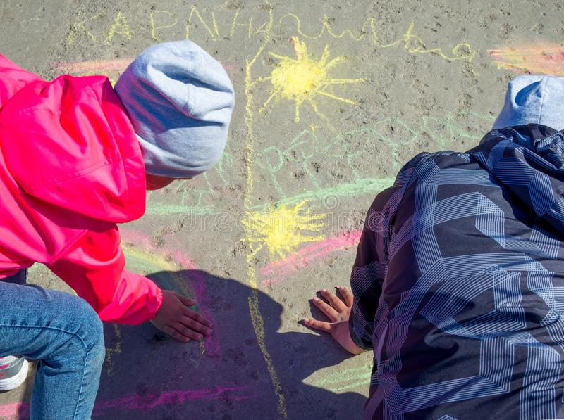 Children draw on the asphalt with colored chalk stock photography
