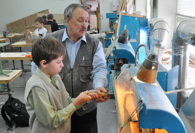 The boy works on a lathe in a school workshop stock photo
