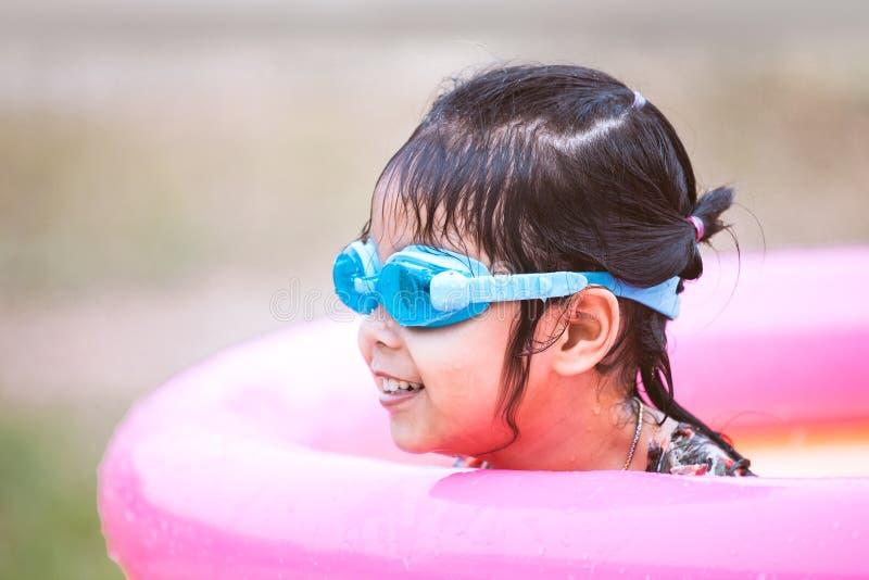 Gafas de la natación de la muchacha asiática feliz del pequeño niño que llevan foto de archivo libre de regalías