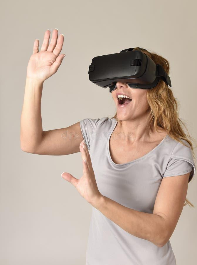 Gafas de la visión de la realidad virtual de las auriculares VR de la mujer que llevan rubia atractiva que miran el vídeo fotografía de archivo