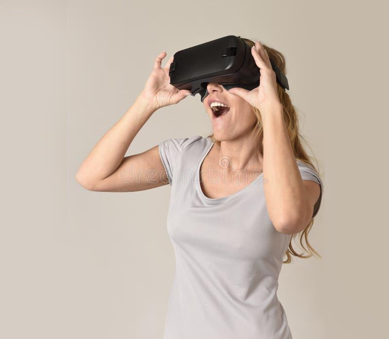 Gafas de la visión de la realidad virtual de las auriculares VR de la mujer que llevan rubia atractiva que miran el vídeo imagenes de archivo