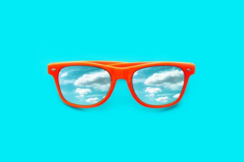 Gafas de sol anaranjadas con el cielo azul con reflexiones de las nubes aislado en fondo azul ciánico intenso imagenes de archivo