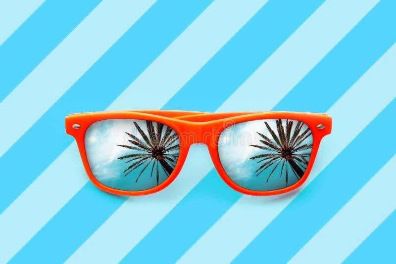 Gafas de sol anaranjadas del verano con reflexiones de las palmeras aisladas en fondo azul con las rayas diagonales foto de archivo libre de regalías