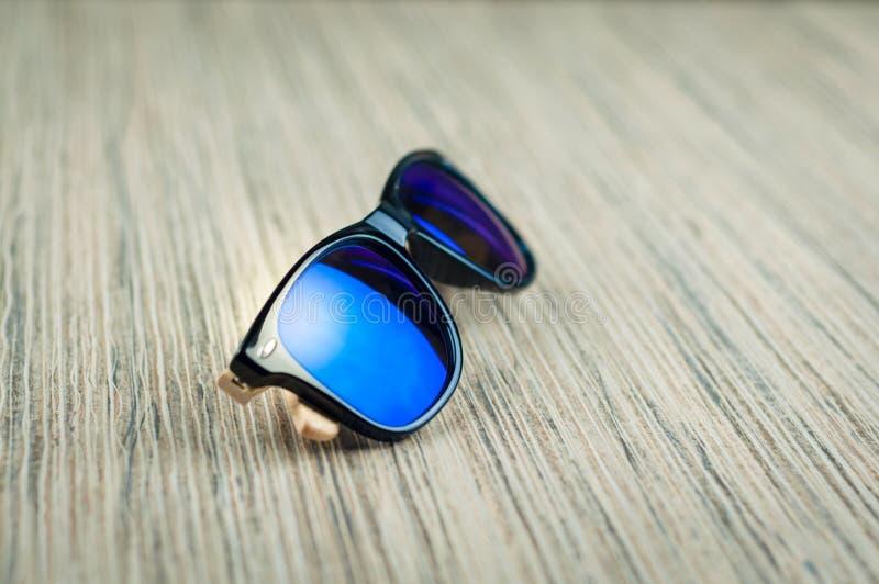 Gafas de sol azules de moda de madera en la tabla imágenes de archivo libres de regalías