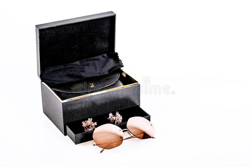 Gafas de sol con las lentes marrones conjuntamente con una caja negra en un fondo blanco fotografía de archivo