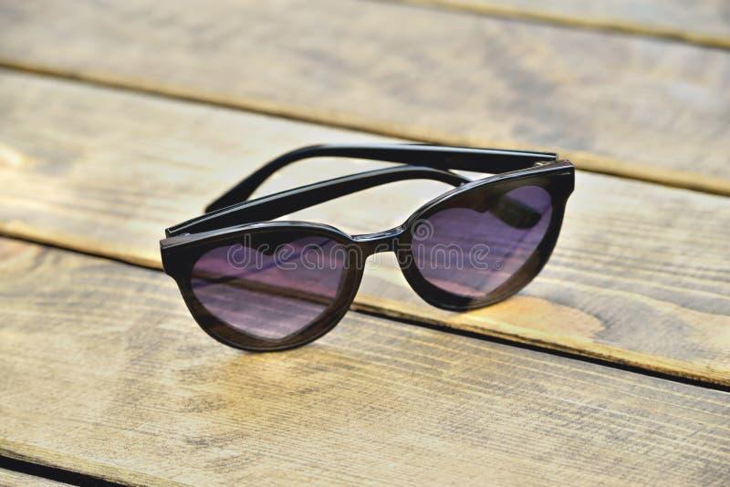 Gafas de sol con los vidrios bajo la forma de corazones en un fondo de madera, concepto fotos de archivo libres de regalías