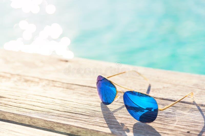Gafas de sol de Blie en decking de madera por la playa foto de archivo